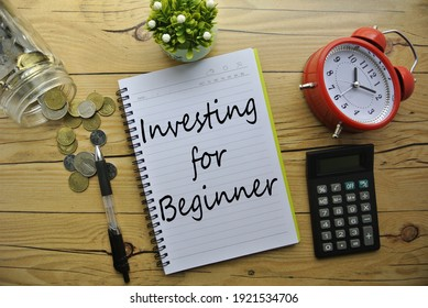 """Selective focus of coin, pen, calculator, plant, watch and notebook written with """"Investing for Beginner"""" on wooden background."""