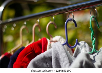Selective focus colorful jacket  hanging on clothesline to dry clothes in the sun with blur green nature background