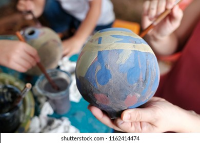 Selective focus at colorful vase. The lift hand holding the globe and right hand using paintbrush to painting water color on the globe. Concept of Art  education. Hobby and activity. Save the earth.