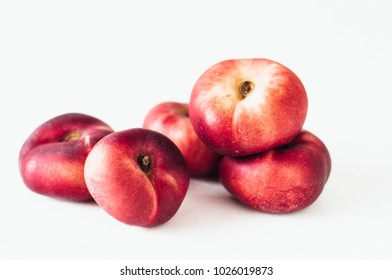 Selective focus composition of several fresh flat donut or red saturn nectarines or ripe fuzzless vineyard peaches on white background