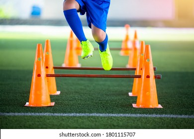 Selective focus to cone and hurdles marker with blurry kid soccer player Jogging and jump cross it. Kid soccer training.