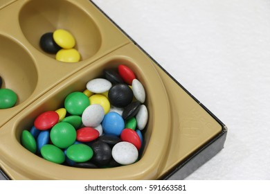 Selective focus, Congkak's templates and it's seeds in white isolated background, Congkak or Congklak is a mancala game of Malay origin played in all over the world.