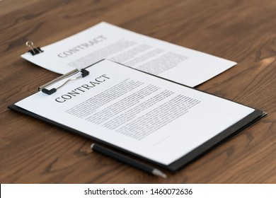 Selective focus of contract in clipboard lying at office on textured and wooden table with copy space