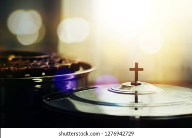 selective focus of the cross on communion tray cover with a wine glasses in communion tray on wooden table against window light with bokeh, christian background with copy space
