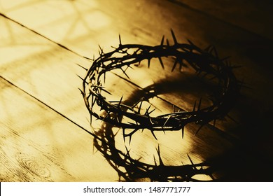 Selective focus  crown of thorns of Jesus Christ on wooden background with window light, Vintage tone with copy space - Shutterstock ID 1487771777