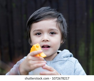 Selective focus of cute little boy holding spray bottle and pointing at the camera, Kid having fun with gardening, Active child activities in garden, A boy spraying water, Children gardening concept