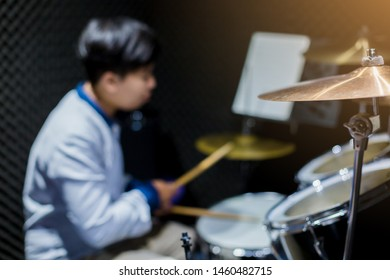 Selective focus to cymbals of drum set with blurry woman play drum set in music room. The concept of musical instrument.