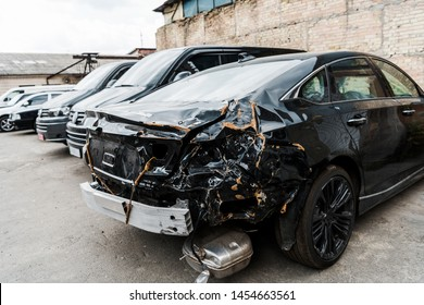 selective focus of damaged black vehicle after car accident near modern automobiles