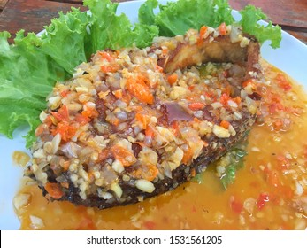 Selective focus of deep fried crispy barramundi fish ,Asian sea bass (Lates calcarifer) with chili ,garlic sauce recipe in Thai style cuisine has sweet ,spicy taste served in white plate in restaurant
