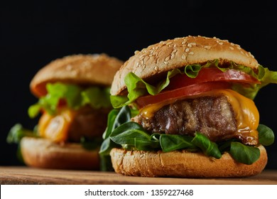 selective focus of delicious meat burgers with cheese and vegetables on wooden chopping board isolated on black