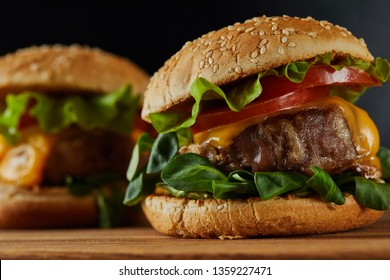 selective focus of delicious meat burgers with cheese and vegetables on wooden chopping board