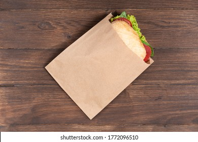 Selective focus. delicious panini in paper bag on wooden background. concept of eco packages of recyclables. still life