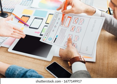 Selective focus of designers developing ux design of website near gadgets on table