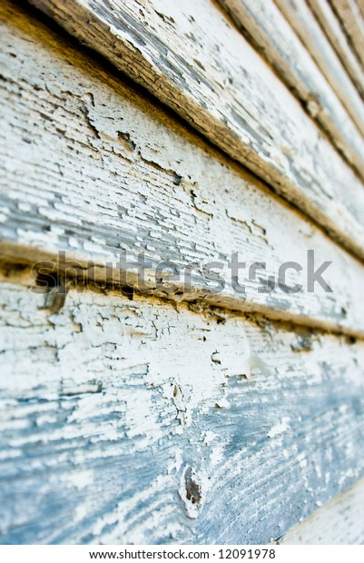 selective focus detail of cracking and peeling paint on ancient wood siding background
