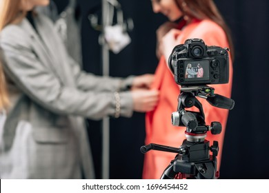 selective focus of digital camera with happy stylist touching jacket on model