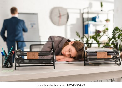 selective focus of document trays with lettering near woman sleeping at desk near, procrastination concept