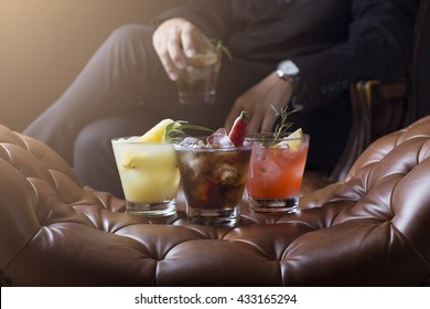 selective focus with dramatic lighting of cocktail on leather sofa with Business man drinking coctail background with soft flare