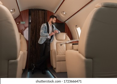 selective focus of dreamy, elegant man holding glass of champagne and looking in porthole in private plane