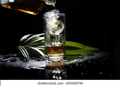selective focus drink alcohol and water glass with dark rum whisky and Sparking water and ice cube with darken background