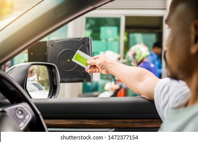 Selective focus to driver hold card to scan at card reader station for open the car park door. stop car and use key card to open the door for safety. security system for parking. The security concept.