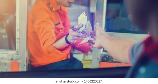 Selective focus to driver pay for the expressway. Man pays money to a cashier for a toll road toll gate motorway entrance. Hand paying express toll way on the road. pay express way.