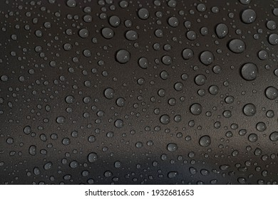 Selective focus of droplet raindrops on a shiny dark grey surface in raining day, Abstract water drop texture, Nature pattern background.