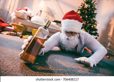 selective focus of drunk bad santa holding bottle of whiskey