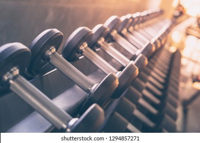 Selective focus of dumbbells in gym with sun flare effect and vintage filter background