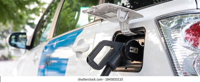 Selective focus at electric taxi car charger plug  while charging battery at the station. Alternative and sustainable power energy for vehicle. Eco friendly modern transportation. Panorama shot.