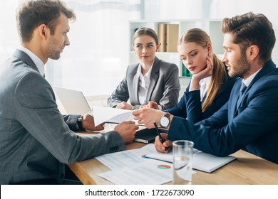 Selective focus of employee with resume during job interview with recruiters in office