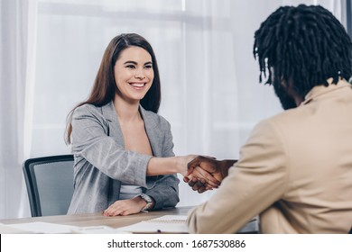 Selective focus of employee smiling and shaking hands with african american recruiter at job interview in office