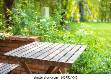 Selective focus of empty wooden table or plank with chair or bench on background for product display.