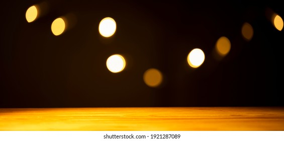 (Selective focus) Empty wooden table illuminated by a warm source of light, black background with a blurred light chain. Empty wooden board with copy space.
