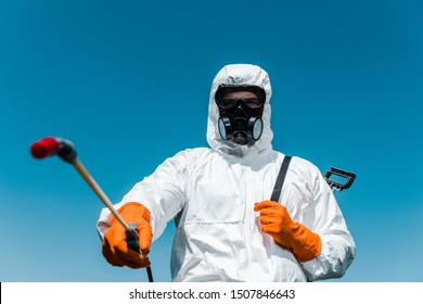 selective focus of exterminator in uniform and latex gloves holding spray outside