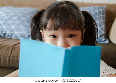 Selective focus the eyes of asian lovely girl looking to camera with funny emotion, Use book to obscure her face in living room