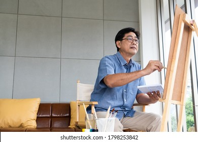 Selective focus at face. Indoor shot of Senior Asian man sit and painting picture inside of the house. Happy retirement lifestyle concept.