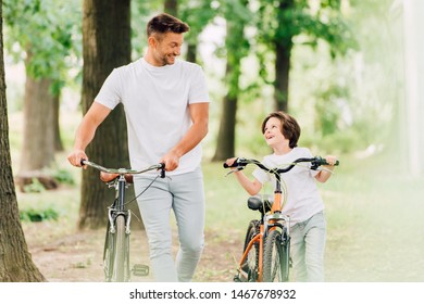 selective focus of father and son with bicycles looking at each other