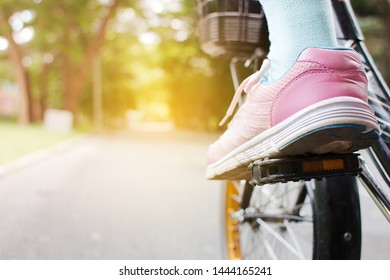 Selective focus feet wearing pink sneaker, riding bicycle on road in park.