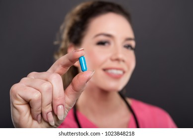 Selective focus of female doctor holding blue pill and smiling on black background