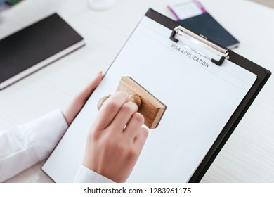 selective focus of female lawyer with stamp in hand holding clipboard with visa application lettering on document