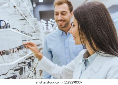 selective focus of female oculist showing eyeglasses on shelves to smiling man in optics