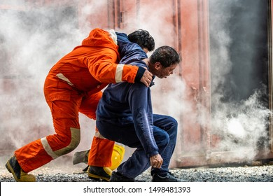 Selective focus firefighter in fire suit on safety rescue duty help a man suffocating smoke in burning premises by first aid emergency and carry him to outside. Safety, rescue and health care concept.