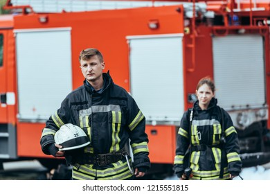 selective focus of firefighters in fireproof uniform on street with fire truck behind
