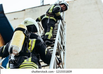 selective focus of firefighters in fireproof uniform standing on ladder