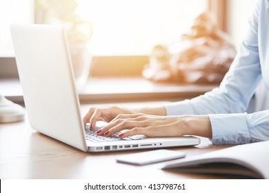 Selective focus, flare sun. Cropped shot of woman's hands with red nails typing on keyboard while chatting with friends using computer laptop sitting against the window. Female manager checking e-mail