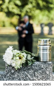selective focus of flowers and mortuary urn on tombstone
