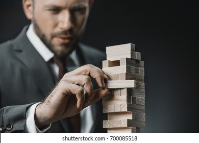 selective focus of focused businessman playing blocks wood game isolated on black