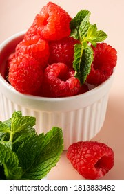 selective focus. fresh raspberries with a sprig of mint. in white fluted clay dishes on a soft pink background