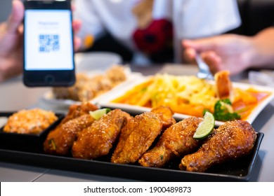 Selective focus to Fried chicken leg with blurry QR code tag on smartphone and customers is eating spaghetti.