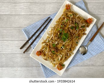 Selective focus of Fried Rice Noodle with smoked beef (Kwetiau Goreng Sapi - Indonesia) in a white plate on a wooden background. Top view. Copy space.